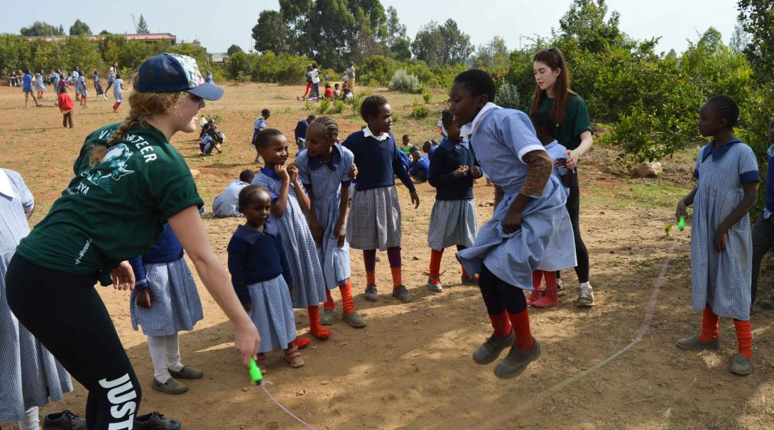 Teenage Projects Abroad care volunteers play with children in Kenya.